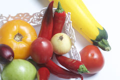Un insieme delle verdure per insalata si trova in un canestro del pizzo Su una priorità bassa bianca Cipolle e pomodori dei color Immagine Stock Libera da Diritti