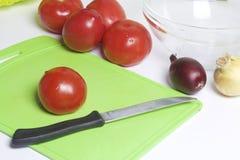 Un insieme delle verdure per insalata si trova vicino al tagliere Coltello per il taglio e un contenitore per insalata Fotografie Stock Libere da Diritti