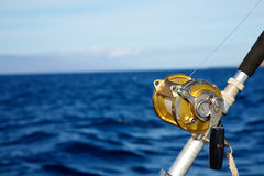 Un insieme di bobina di pesca contro l'oceano blu Fotografia Stock Libera da Diritti