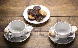 Un insieme di due tazze ceramiche del tè con le bustine di tè ed i piatti dei biscotti Preparazione per fare tè Immagine Stock