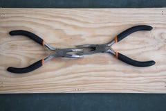 Un insieme di due tenaglie su fondo di legno Fotografia Stock Libera da Diritti