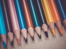 Un insieme di parecchie matite colorate Matite in una fila su una superficie di legno Fotografia Stock Libera da Diritti