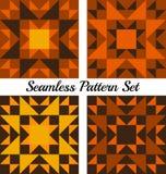 Un insieme di quattro modelli senza cuciture geometrici di Halloween con i triangoli ed i quadrati delle tonalità arancio, gialle Immagini Stock Libere da Diritti