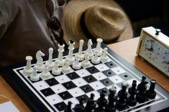 Un insieme di scacchi con i fori speciali per i viaggiatori e per i ciechi ? sulla tavola accanto all'orologio, al cappello dello immagini stock