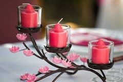 Un insieme di tre candele come pezzo di centro della Tabella Fotografie Stock