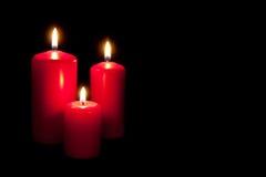 Un insieme di tre candele rosse che bruciano nello scuro Fotografia Stock