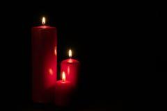 Un insieme di tre candele rosse che bruciano nello scuro Fotografie Stock