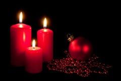 Un insieme di tre candele rosse con le sfere di natale Immagine Stock