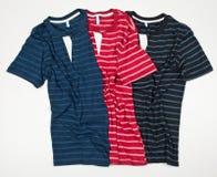 Un insieme di tre ha barrato le magliette per gli uomini su fondo bianco fotografia stock