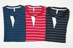 Un insieme di tre ha barrato le magliette per gli uomini su fondo bianco immagine stock libera da diritti
