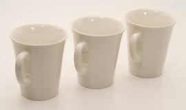 Un insieme di tre tazze bianche Fotografia Stock Libera da Diritti