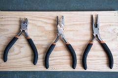 Un insieme di tre tenaglie su fondo di legno Fotografia Stock