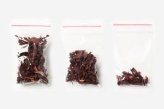 Un insieme di tre VUOTI, MEZZE E borse trasparenti di plastica PIENE della chiusura lampo con il tè del carcade isolato su bianco Fotografie Stock Libere da Diritti