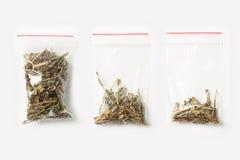 Un insieme di tre VUOTI, MEZZE E borse trasparenti di plastica PIENE della chiusura lampo con il tè di fioritura di battuta isola Immagini Stock Libere da Diritti