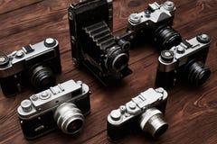 Un insieme di varie macchine fotografiche d'annata sopra fondo di legno Immagini Stock