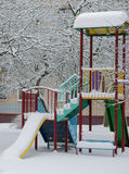 Un insieme solo dell'oscillazione, campo da giuoco, inverno sotto la neve, nell'iarda della città fotografia stock libera da diritti