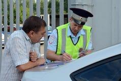 Un inspecteur du service de patrouille de police de route rédige un rapport sur la violation des règles de la circulation Photos stock
