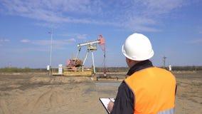 Un inspecteur-opérateur masculin dans un gilet de signal et un casque blanc enregistre les lectures au sujet du pétrole de dispos banque de vidéos