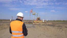 Un inspecteur-opérateur masculin dans un gilet de signal et un casque blanc enregistre les lectures au sujet du pétrole de dispos clips vidéos