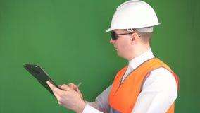 Un inspector de sexo masculino con una tableta escribe y marca comentarios sobre un objeto de la construcción, fondo verde, llave metrajes