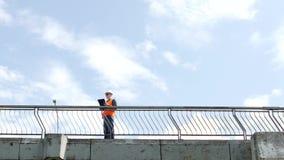 Un inspector del hombre camina a través del puente que mira alrededor y examina la calidad del puente, controles, ingeniero almacen de metraje de vídeo