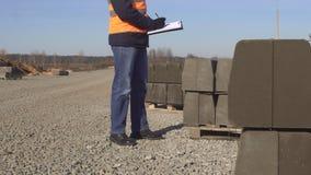 Un inspector en un chaleco de la señal y un casco blanco con los vidrios negros hace notas en su carpeta en la calidad del camino almacen de metraje de vídeo