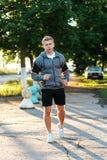 Un instructor masculino está corriendo abajo de los auriculares que llevan del camino Corredor por la mañana en el parque Escucha Fotos de archivo libres de regalías