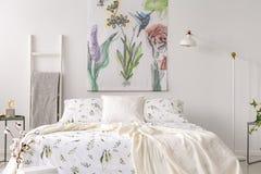 Un intérieur en pastel de chambre à coucher avec un lit s'est habillé en toile de blanc de modèle de plantes vertes Tissu peint e photos stock