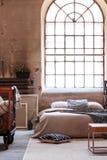 Un intérieur industriel de chambre à coucher avec une grande fenêtre et un double lit photo stock