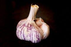 Un'intera metà ha aperto l'aglio bianco e porpora Immagini Stock Libere da Diritti