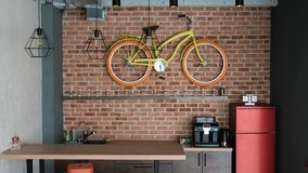 un interno moderno reale nello stile del sottotetto Nella cucina c'è una barra, un frigorifero e una bicicletta decorativa stock footage