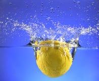 Un intero limone che spruzza nell'acqua Immagine Stock