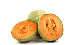 Un intero melone del cantalupo e due metà immagini stock