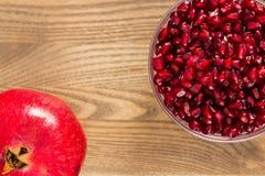 Un intestino dei semi del melograno accanto ad un'intera frutta del melograno Fotografie Stock