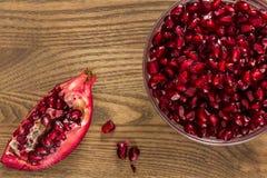 Un intestino dei semi del melograno accanto ad un pezzo di frutta del melograno Immagini Stock