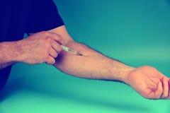 Un intoxiqué masculin d'intoxiqué s'injecte en intraveineuse pour le plaisir photos libres de droits