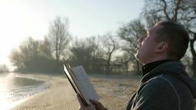 Un invalide dans le fauteuil roulant avec livre sacré, prie le handicapé, personne malade tient la bible dans des mains, espoir d banque de vidéos