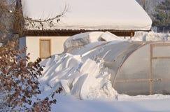Un invernadero y una casa en el jardín Fotos de archivo