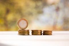 Un inverso di 1 euro moneta, stante dal suo lato, su una pila di eurocents Immagine Stock Libera da Diritti