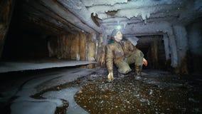 Un investigador con una linterna examina una mina abandonada vieja, helada almacen de metraje de vídeo