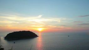 Un'isola tropicale nel mare al tramonto Insiemi rossi del sole sopra l'orizzonte stock footage