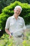 Un jardinier plus âgé avec le tuyau flexible Images libres de droits