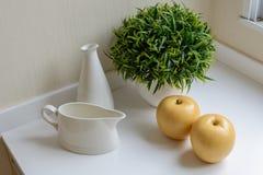 Un jarro con la botella, la manzana y el decorativ Fotografía de archivo