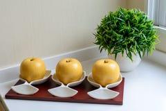 Un jarro con la manzana y la planta decorativa Fotos de archivo