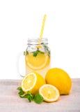 Un jarro de cristal grande con limonada y limones amarillos en una tela ligera, en un fondo blanco Foto de archivo libre de regalías