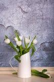 Un jarro de la lata llenado de los tulipanes blancos Fotografía de archivo