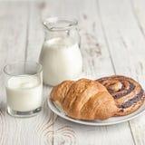 Un jarro de la leche y de un cruasán apetitoso en una tabla del pueblo en el ligh de la mañana fotografía de archivo