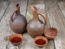 Un jarro del vino y un sistema georgianos tradicionales de tazas de la arcilla Imágenes de archivo libres de regalías