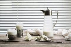 Un jarro y un vidrio viejos con leche en una tabla de madera Fotografía de archivo