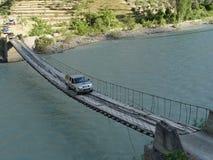 Un jeep conduce sobre un puente de cuerda sobre un río foto de archivo